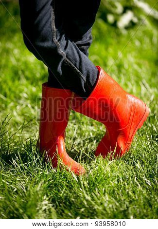 Closeup Of Girl In Red Rubber Boots Posing On Fresh Green Grass