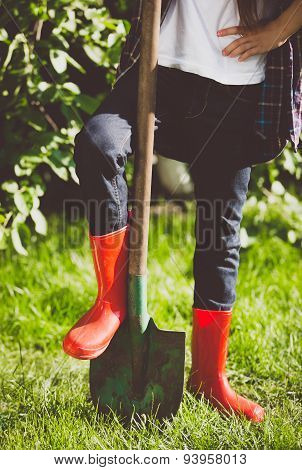 Toned Photo Of Young Woman Holding Leg In Rubber Boots On Shovel
