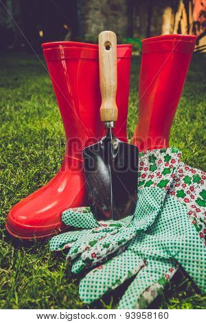 Toned Filter Of Garden Tools And Red Boots On Meadow