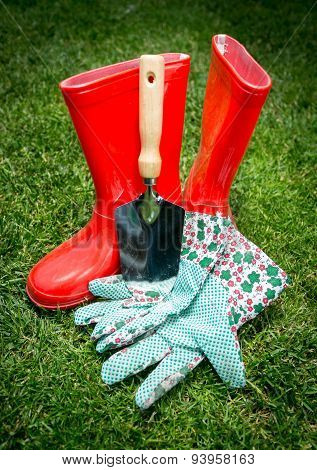 Closeup Of Spade, Gloves And Red Rubber Boots Lying On Grass