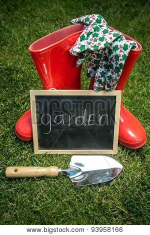 Blackboard On The Grass Next To Garden Tools With Text