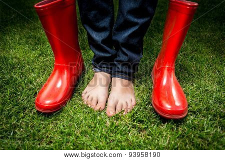 Female Feet Standing On Green Grass Next To Red Rain Boots