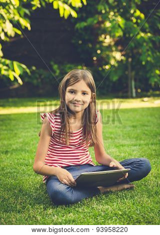 Toned Photo Of Cute Girl Sitting On Lawn And Using Digital Tablet