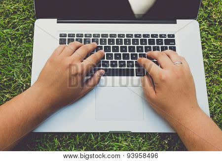Toned Shot Of Man Lying On Grass And Using Laptop