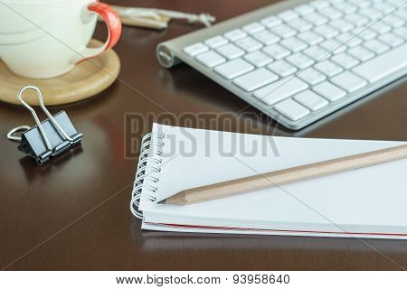 Notepad With Pencil In Workspace And Keyboard