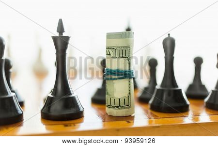 Closeup Of Rolled Dollars On Place O Black Chess Piece