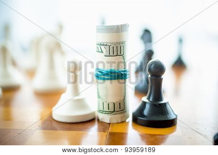 Twisted Dollar Bills Standing On Chess Board Between White And Black Pieces