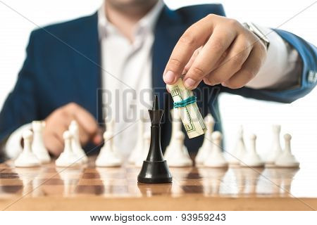 Businessman In Suit Make Move With Dollars In Chess Game