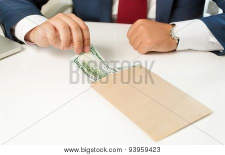 Businessman Pulling Banknote Out Of Envelope Lying On Table
