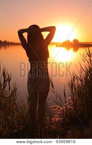 Girl at the lake at sunset