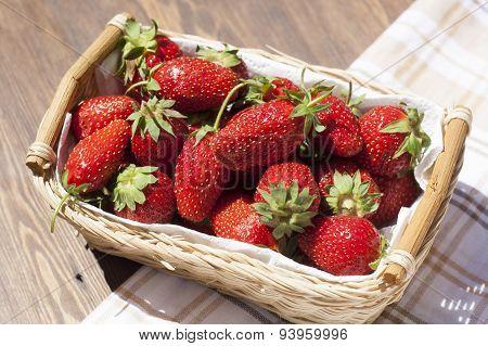 Fresh strawberries with green tails wickerwork basket