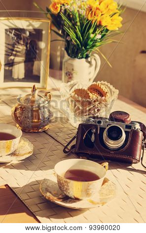 Toned background with Cup of tea summer flowers old foto and vintage camera