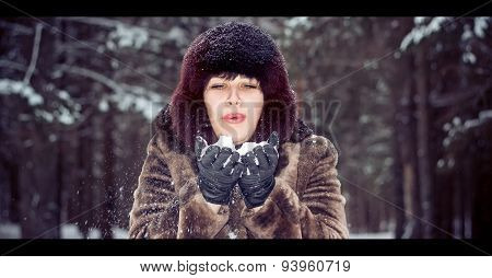 Girl blows away the snow from
