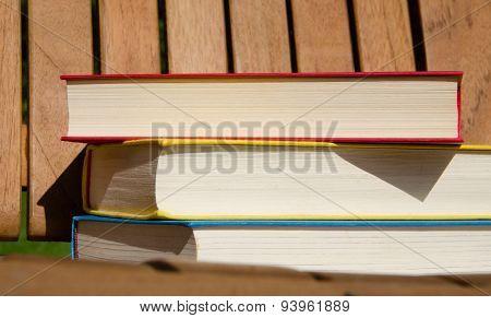 Red, yellow and blue books on a wooden chair
