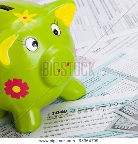 Hundred Usa Dollars Banknote And Piggy Bank Over Us Tax Form