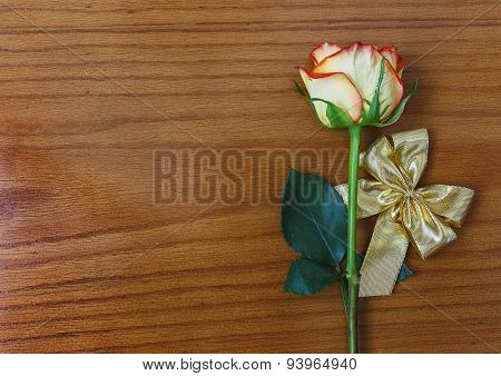 Rose And Gold Decorative Bow On The Wooden Background