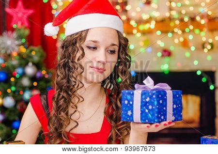 Beautiful Girl Looking At Christmas Gift