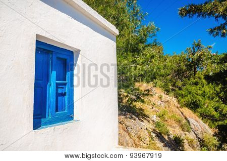Blue wooden window against clear white wall