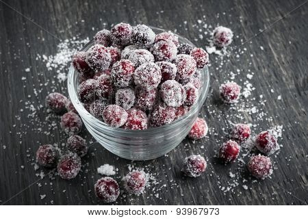 Sugared cranberries holiday dessert in bowl on rustic wooden background