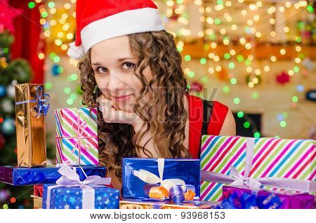 Beautiful Girl At A Table With Christmas Gifts