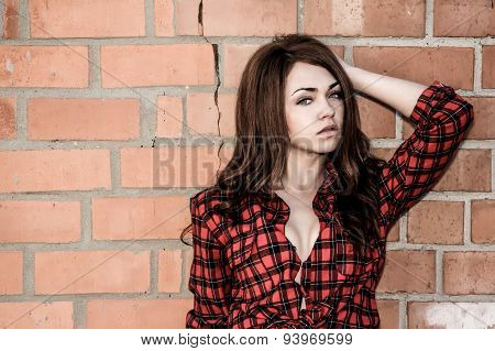 Beautiful Young Woman In A Shirt At The Background Of The Wall
