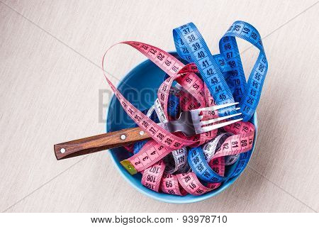 Many Colorful Measuring Tapes In Bowl On Table
