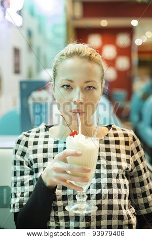 Woman drinking milk shake in diner.