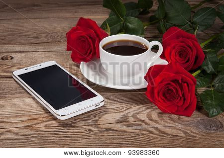 Smartphone, A Cup And Roses On Old Table