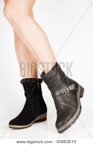 Beautiful female legs in the different leather boots with buckles