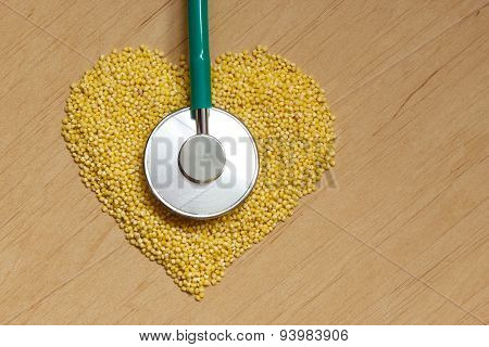 Millet Groats Heart Shaped On Wooden Surface.