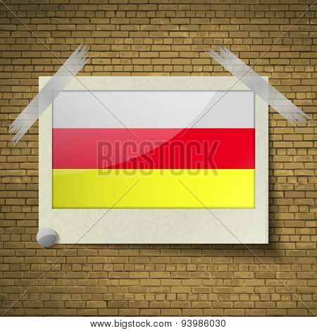 Flags North Ossetiaat Frame On A Brick Background. Vector