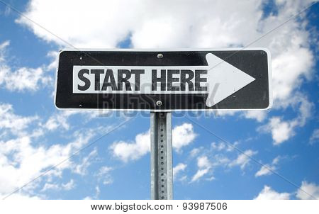 Start Here direction sign with sky background