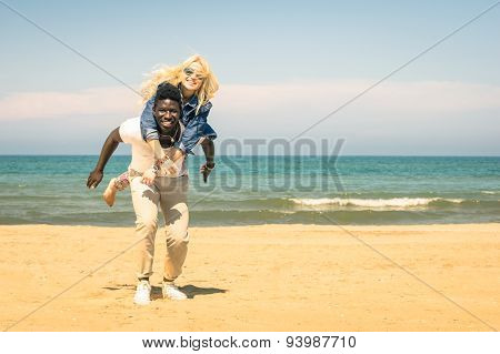 Young Multiracial Couple At The Beach Having Fun With Piggyback Jump - Happy Mixed Race Relationship
