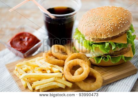 fast food and unhealthy eating concept - close up of hamburger or cheeseburger, deep-fried squid rings, french fries, coca cola drink and ketchup on wooden table