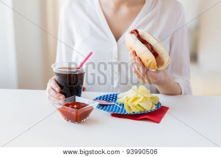 american independence day, celebration, patriotism and holidays concept - close up of woman hands holding hot dog and coca cola in plastic cup with potato chips and ketchup on 4th july at home party