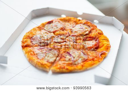 fast food, italian kitchen and eating concept - close up of pizza in paper box on table