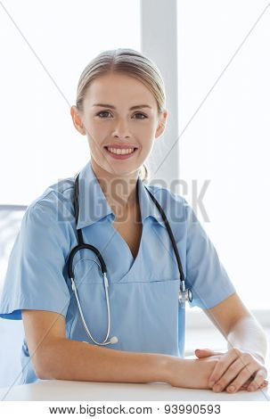 health care, profession, people and medicine concept - happy female doctor or nurse with clipboard at hospital