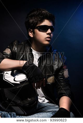 Portrait of pretty boy wearing stylish leather jacket, sunglasses and holding helmet posing in the studio over blue background, fashion for bikers