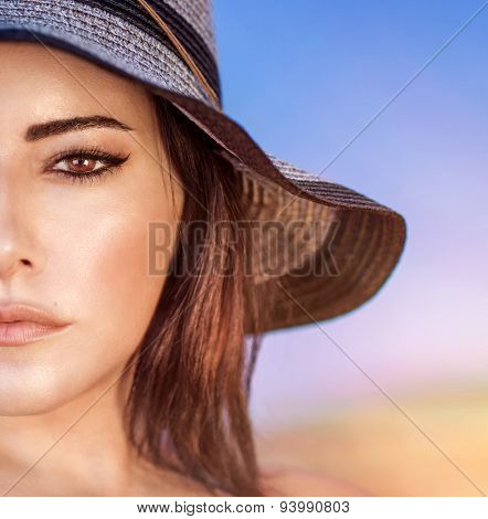 Closeup portrait of gorgeous beautiful arabic woman with perfect makeup wearing stylish hat on the beach, half face, fashion and beauty