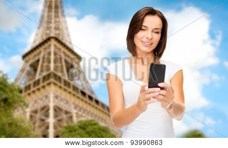 people, technology, tourism and travel concept - young woman taking selfie with smartphone over paris eiffel tower background