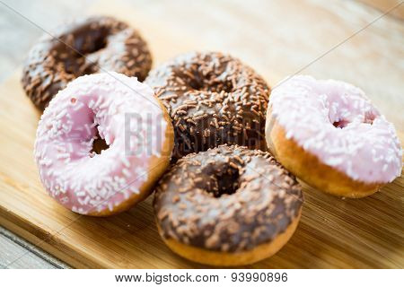 food, junk-food and eating concept - close up of glazed donuts on wooden board