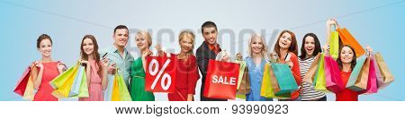 consumerism, people and discount concept - group of happy people with percentage and sale sign on shopping bags over blue background
