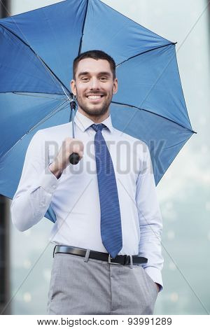 business, bad weather and people and concept - young smiling businessman with umbrella outdoors