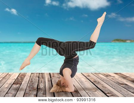 sport, fitness, yoga, people and health concept - happy young woman doing headstand exercise on wooden berth over sea and blue sky background