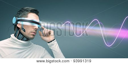 people, technology, future and progress - man in futuristic 3d glasses and microchip implant or sensors over gray background with laser light and electromagnetic waves
