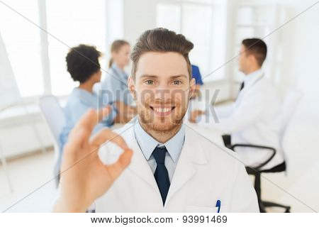 clinic, profession, gesture, people and medicine concept - happy male doctor showing ok hand sign over group of medics meeting at hospital