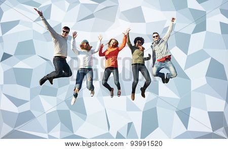 people, freedom, happiness and teenage concept - group of happy friends in sunglasses jumping high over gray low poly background