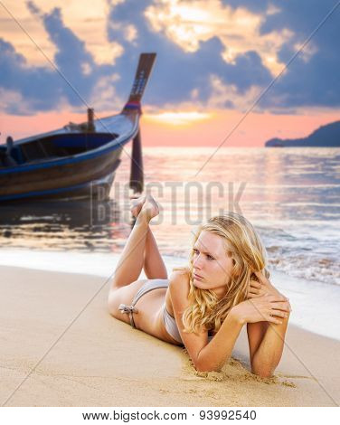 Beautiful young blonde woman in bikini laying on the beach at sunset with lon tail boat on background