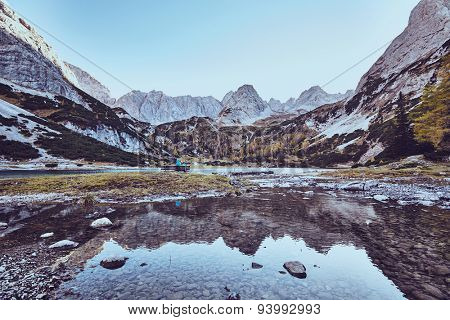 Magnificent landscape with female tourist resting on bench near mountain lake