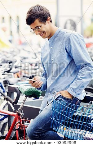 Cheerful young man in glasses and blue shirt with hand in pocket typing message by mobile phone leaning on railing on bicycle parking